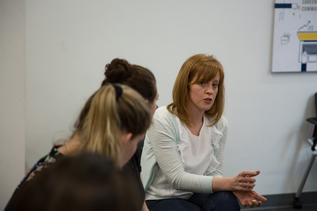 A woman speaks with Organizational Science and Communications students.