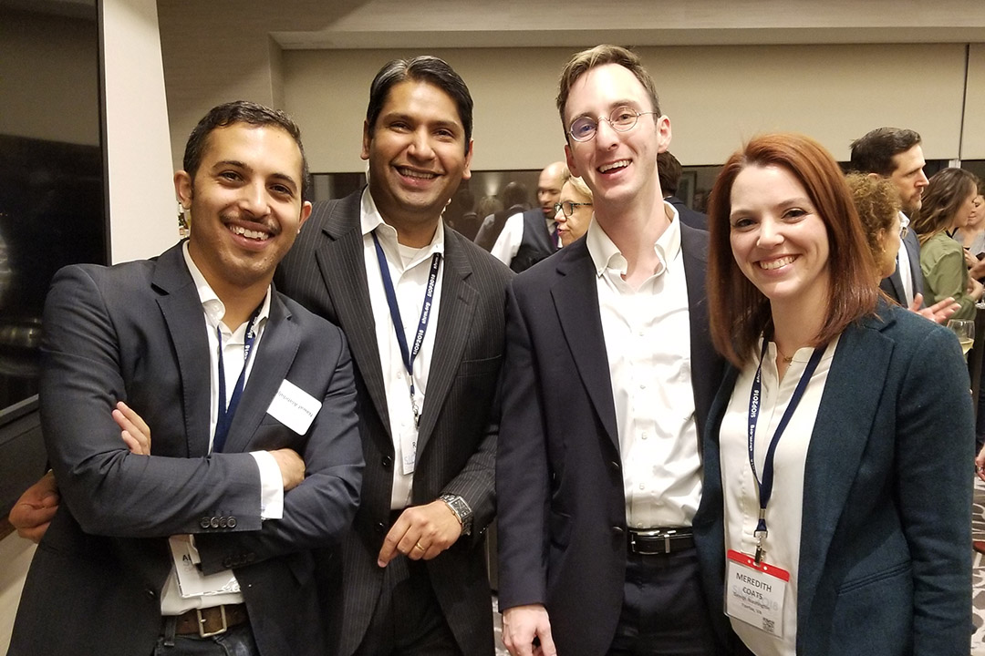 A group of four students in business suits smiling at a conference